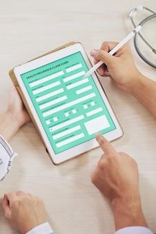 Agent wypełniający formularz ubezpieczenia zdrowotnego z pacjentem