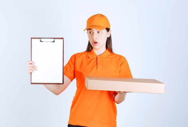 Agentka obsługi w pomarańczowym stroju trzymająca kartonowe pudełko po pizzy na wynos i prosi o podpis, wyglądając na zdezorientowaną