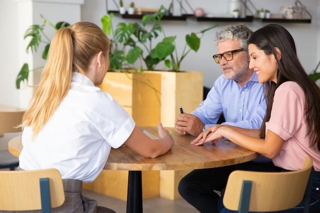 Agentka prezentująca treści na tablecie kilku młodym i dojrzałym klientom