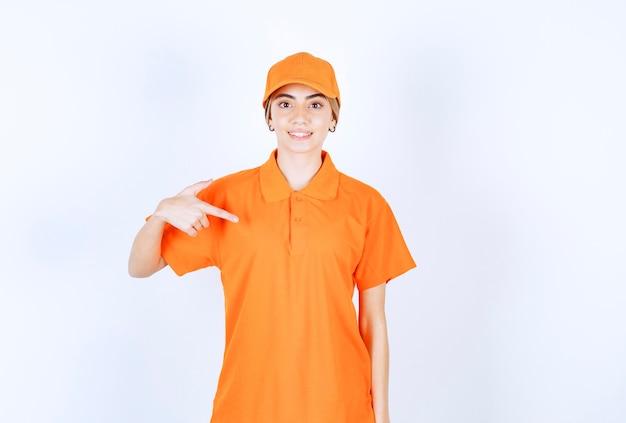 Agentka usług w pomarańczowym mundurze, wskazująca na siebie