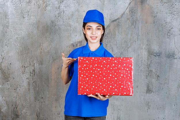 Agentka usługowa w niebieskim mundurze trzymająca czerwone pudełko z białymi kropkami, pokazująca i zapraszająca bliską osobę do wręczenia prezentu.