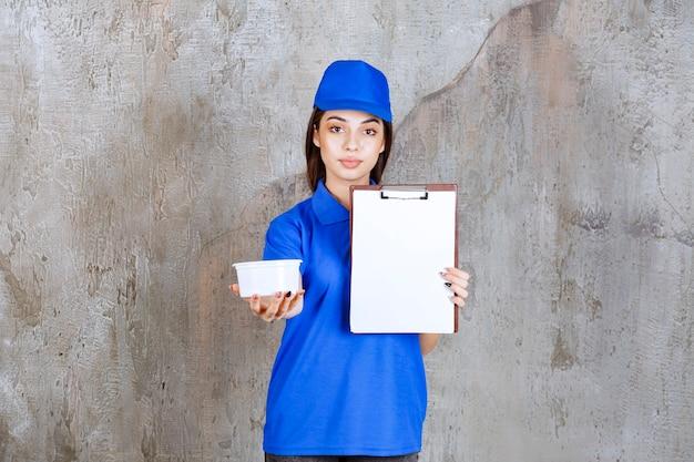 Agentka usługowa w niebieskim mundurze trzymająca plastikową miskę i prosząca o podpis