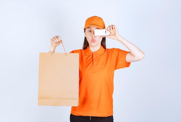 Agentka usługowa w pomarańczowym dresscode trzymająca kartonową torbę na zakupy i prezentująca swoją wizytówkę
