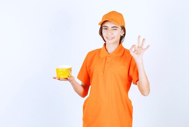 Agentka usługowa w pomarańczowym mundurze trzymająca żółtą filiżankę na wynos i delektująca się smakiem