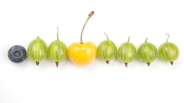 Agrest i inne jagody na białej powierzchni. przydatne witaminy zdrowe jedzenie owoce. zdrowe śniadanie warzywne