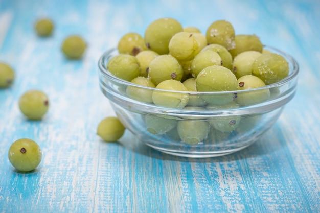 Agrest marznący jagody w pucharze szkła na rocznika stole.