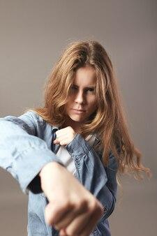 Agresywna brązowowłosa dziewczyna ubrana w białą koszulkę i dżinsy trzyma ręce w pięści na szarym tle.