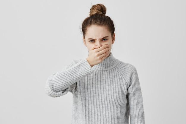 Agresywna dziewczyna o zły wygląd marszcząc brwi, zakrywając usta dłońmi. wściekłość zwykłego klienta wyrażającego nieporozumienie, próbującego nie walczyć. koncepcja relacji międzyludzkich