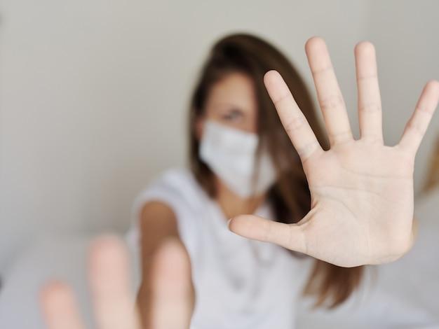 Agresywna kobieta w masce medycznej zakrywa aparat rękami na jasnym tle pandemii