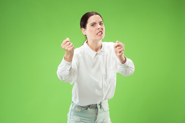 Agresywny biznes kobieta stojąca na białym tle na modnej zielonej ścianie studio