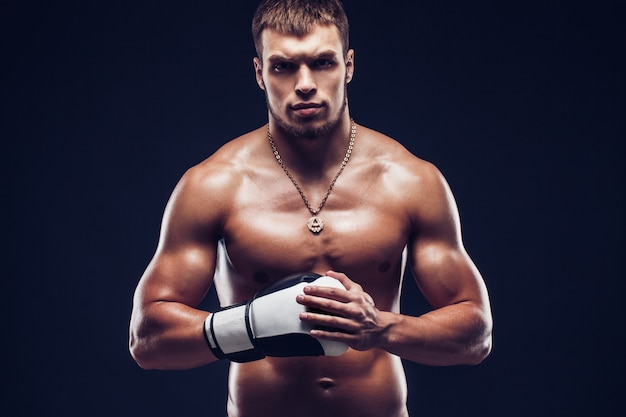 Agresywny bokser bez koszuli na szarym tle.