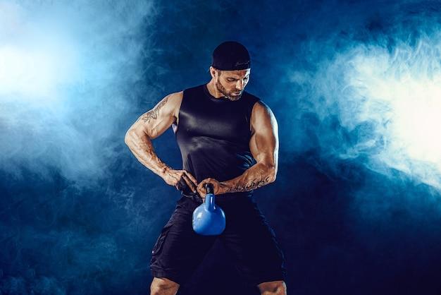 Agresywny, brodaty muskularny kulturysta robi ćwiczenia na biceps z kettlebell.