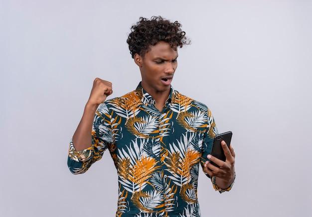 Agresywny i wściekły ciemnoskóry mężczyzna z kręconymi włosami w liściach w koszulce z nadrukiem przegrywa grę na telefonie komórkowym z zaciśniętymi pięściami
