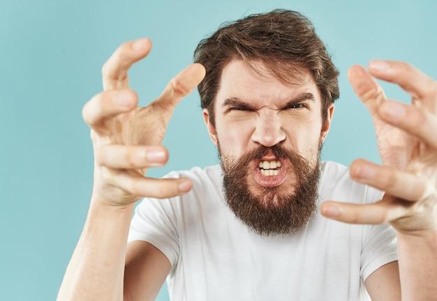 Agresywny mężczyzna krzyczy na niebieskim tle stres drażliwość emocje impulsywne