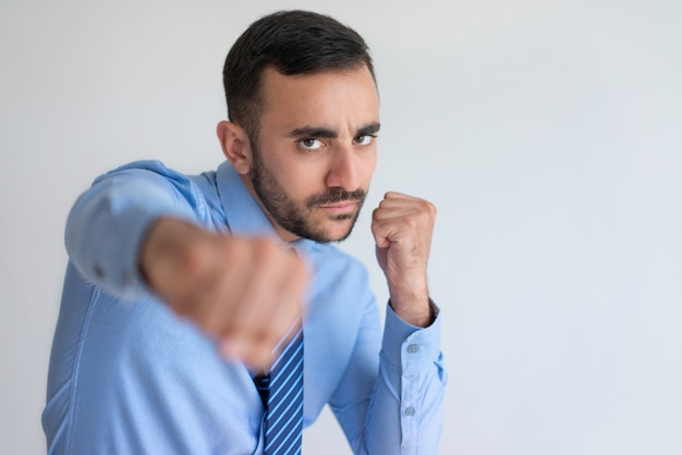 Agresywny młody brodaty biznesmen uderza pięścią kamerę