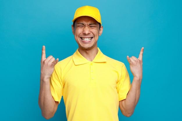 Agresywny młody człowiek ubrany w mundur i czapkę robi rockowy znak