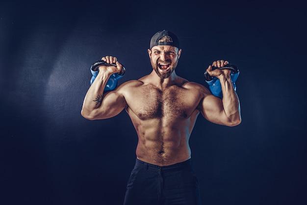 Agresywny, Muskularny, Brodaty Kulturysta Wykonujący ćwiczenia Na Mięśnie Ramion, Naramienny Z Kettlebellem. Strzał Premium Zdjęcia