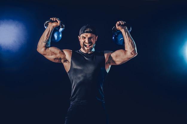 Agresywny, muskularny, brodaty kulturysta wykonujący ćwiczenia na mięśnie ramion, naramienny z kettlebellem. strzał