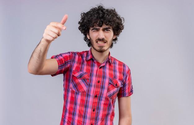 Agresywny przystojny mężczyzna z kręconymi włosami w kraciastej koszuli, wskazując na aparat palcem wskazującym