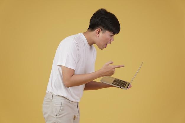 Agresywny zły zdenerwowany wściekły młody azjatycki człowiek zbeształ krzycząc na laptopie na białym tle