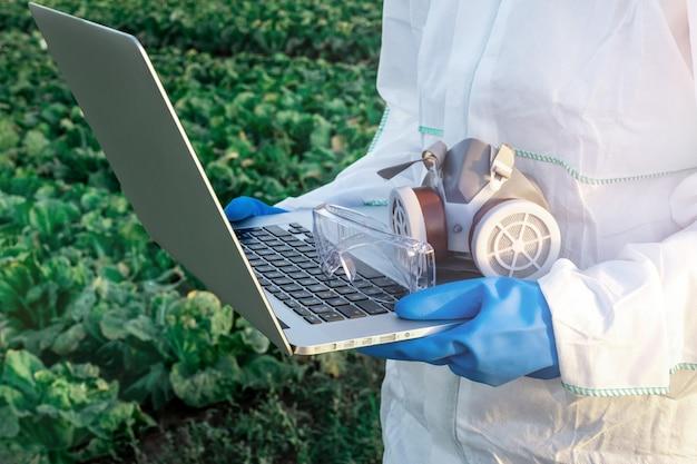 Agronom ubrany w biały kombinezon ochronny, maskę i niebieskie rękawiczki trzyma laptopa na tle pola z żniwami. problemy koncepcji chemii i pestycydów.