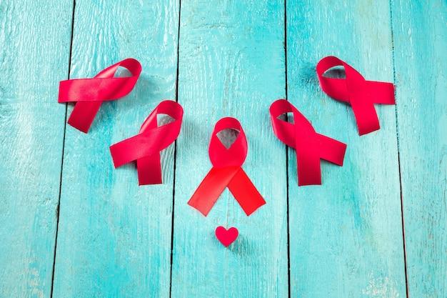 Aids znak świadomości czerwone wstążki na niebieskim tle drewnianych. światowy dzień walki z aids. zdrowie, pomoc, opieka, wsparcie, nadzieja, choroba, koncepcja opieki zdrowotnej
