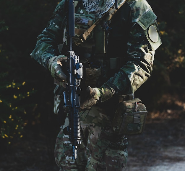 Airsoft wojskowy gracz w mundurze kamuflażu z uzbrojonym karabinem szturmowym.