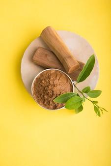 Ajurwedyjska pasta chandan lub drzewo sandałowe w srebrnej misce z patyczkami i liśćmi umieszczonymi na sahanor sahana lub okrągłej kamiennej podstawie do tworzenia pasty