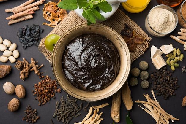 Ajurwedyjski chyawanprash jest potężnym wzmacniaczem odporności lub naturalnym suplementem zdrowotnym. podawane w antycznej misce ze składnikami, na nastrojowym tle, selektywne skupienie