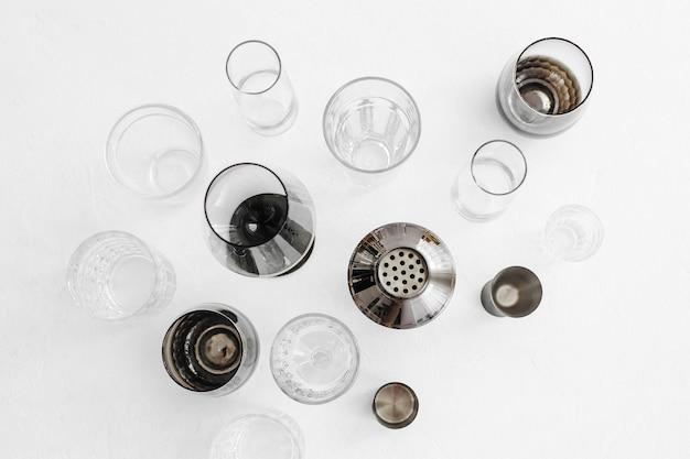 Akcesoria barowe i narzędzia do robienia koktajli. shaker, jigger, szkło, łyżka i inne narzędzia barowe. płaski świeckich, widok z góry.