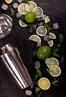 Akcesoria barowe i składniki do drinka koktajlowego limonka, mięta, lód.