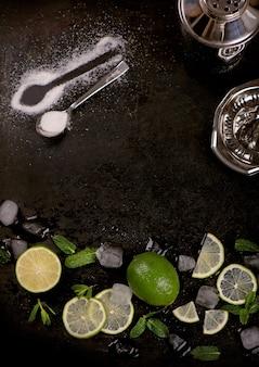 Akcesoria barowe i składniki do koktajlu limonka, mięta, lód.