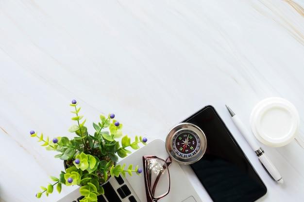 Akcesoria biznesowe na biurku, telefonie komórkowym, laptopie, piórze, filiżance kawy, szklankach, kompasie i doniczce