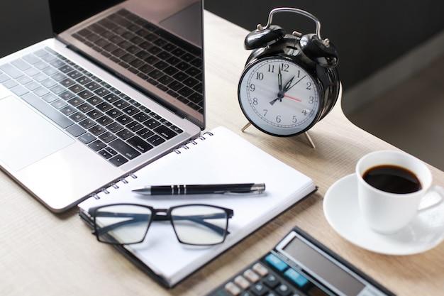 Akcesoria biznesowe na drewnianym biurku, laptopie, okularach, długopisie, książce, filiżance kawy, kalkulatorze i budziku