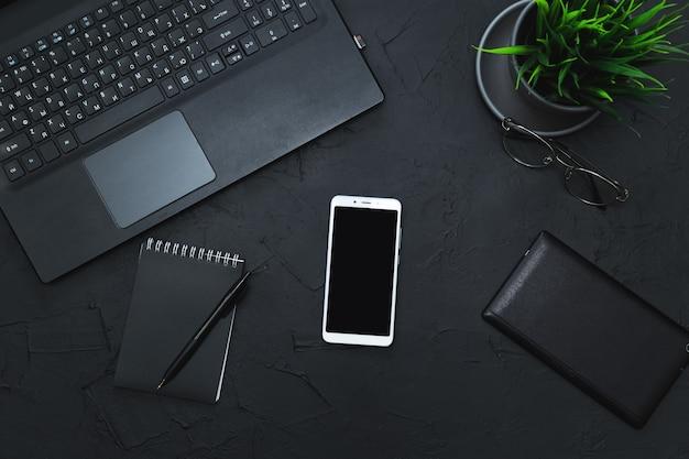 Akcesoria biznesowe na grafitowym stole. biznes, praca na odległość, koncepcja samokształcenia. widok z góry, płaski układ, niski klucz.