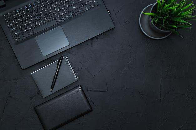 Akcesoria biznesowe na grafitowym stole. biznes, praca na odległość, koncepcja samokształcenia. widok z góry, płaski układ.