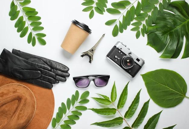 Akcesoria damskie, aparat retro, figurka wieży eiffla na białym tle z zielonymi liśćmi.