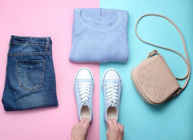 Akcesoria damskie, buty odzieżowe na pastelowym stole. dżinsy, sweter, torba. damskie dłonie trzymają tenisówki. kreatywne mieszkanie leżało. widok z góry. minimalizm