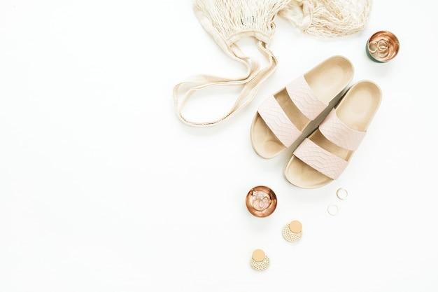 Akcesoria damskie: kapcie, woreczek, kolczyk i pierścionki na białej powierzchni