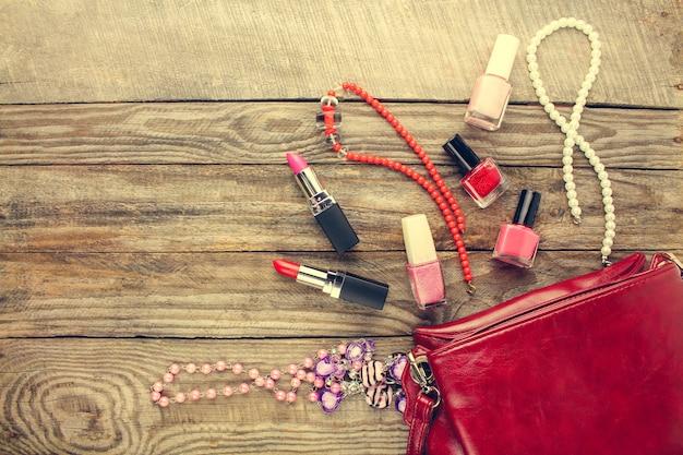 Akcesoria damskie: kosmetyczka, naszyjnik, lakier do paznokci, szminka. widok z góry. stonowany obraz.