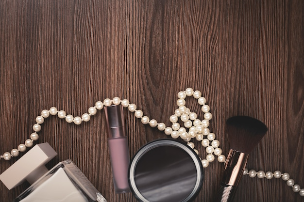 Akcesoria damskie: perfumy, pędzel, naszyjnik