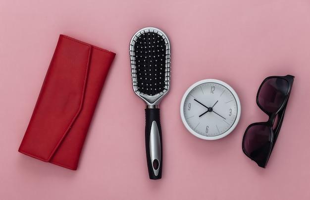 Akcesoria damskie. portfel, grzebień, okulary przeciwsłoneczne i zegar na różowo.