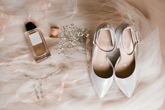 Akcesoria damskie: szare buty, woda toaletowa, biżuteria kostiumowa i gałązka łyszczec na białym tiulu. poranek panny młodej