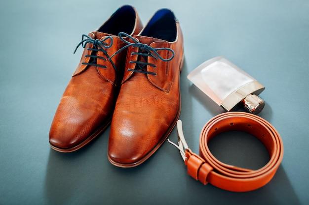 Akcesoria dla biznesmenów. brązowe skórzane buty, pasek, perfumy. moda męska. biznesmen