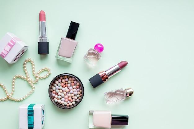 Akcesoria dla kobiecej urody. makijaż, lakier do paznokci, butelka perfum, wszystko na pastelowej ścianie. minimalistyczne kosmetyki wall. biżuteria kobieca. profesjonalny makijaż kobiecy