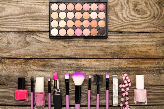 Akcesoria dla kobiet: kosmetyczka, pędzle do makijażu, naszyjnik, lakier do paznokci, szminka.
