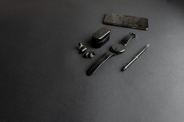 Akcesoria dla męskiej urody na monochromatycznym tle. czarny długopis, czarny inteligentny zegarek, smartfon i bezprzewodowe słuchawki na ciemnym tle. widok z góry. minimalistyczny czarny trend 2020.