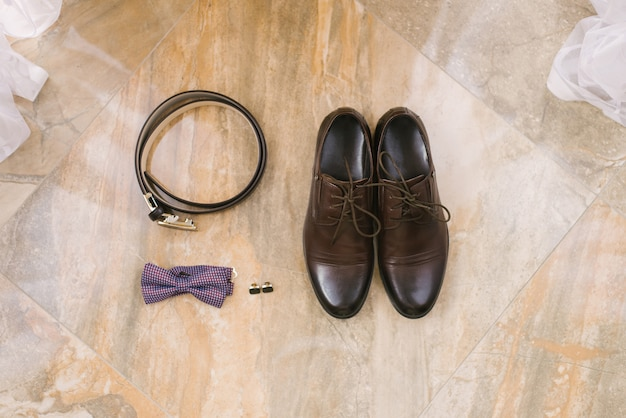 Akcesoria dla pana młodego: brązowe buty ze sznurowadłami, spinki do mankietów, pasek i fioletowa muszka na beżu
