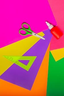 Akcesoria do aplikacji. nożyczki, klej, kolorowy papier i linijka. widok z góry.