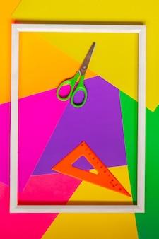 Akcesoria do aplikacji. nożyczki, rama, kolorowy papier i linijka. widok z góry.
